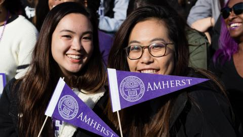 Two students at a Homecoming game, holding Amherst flags