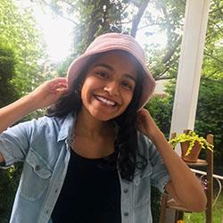 Jackie smiling, wearing a jean jacket and bucket hat