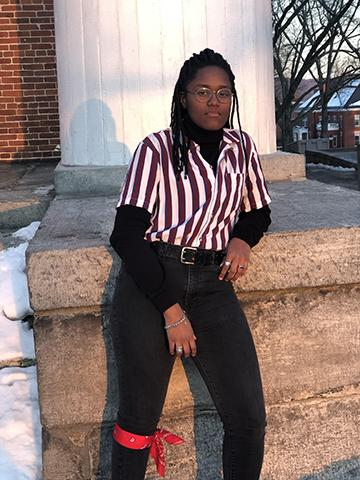 picture of Noni Akintunde, wearing dark jeans, white and red stripped button up in front of Johnson Chapel (stone pillar)
