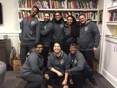 Staff and students pose smiling in the Queer Resource Center