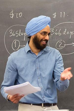 Singh in front of a blackboard