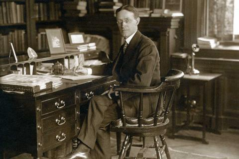 Alexander Meiklejohn sitting behind his desk
