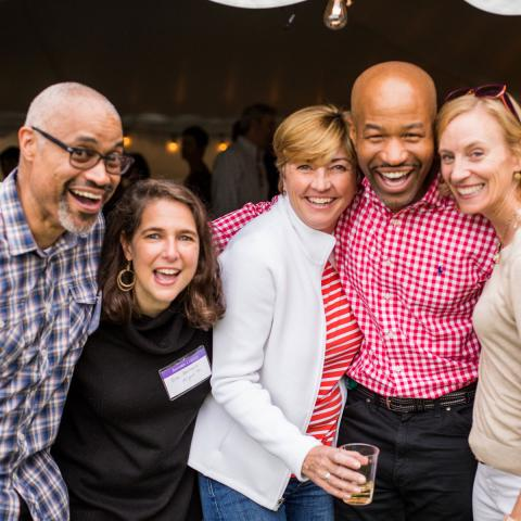 Five alumni friends smiling at Reunion