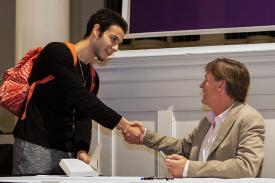 An Amherst student shakes hands with author Michael Lewis