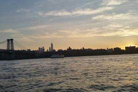 Sunset over water with a city scape in the background