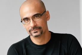 Junot Diaz wearing glasses and a black shirt