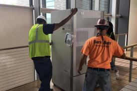 Workmen moving refrigerators into the new Science Center