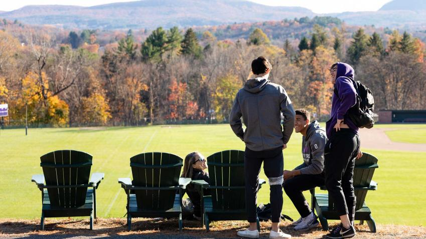 Four students gathered by the adirondack chairs overlooking the Mount Holyoke range