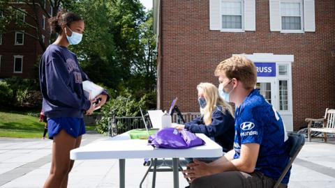 two students sit at a voter registration table outside at Amherst College