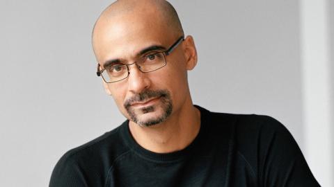 Junot Diaz wearing glasses and a black shirt