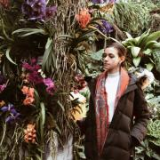 Nisan stands in a colorful garden, looking at the brightly colored plants next to her