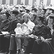A black and white photo of graduation with a man holding a baby