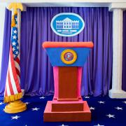 A miniature clay sculpture of the White House podium next to an American flag