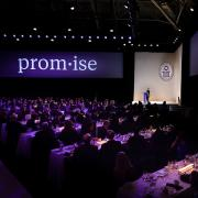 "A large stage in purple light with the word ""promise"" projected on a big screen"