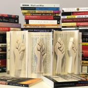 Books with a raised fist sculpted into the fore edge