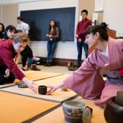 The ceremony leader, dressed in a kimono, hands a cup of tea to a student