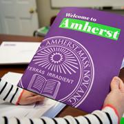 A photo of a person's hands holding an Amherst College brochure