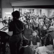 A black and white photo of a woman speaking to a large crowd inside a library