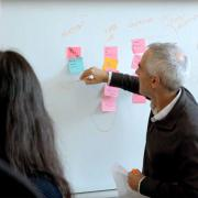 Matthew Glickman working at a whiteboard with students