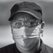 A woman in a hat and glasses wearing a mask