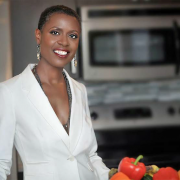 A Black woman in a white suit jacket standing in a kitchen