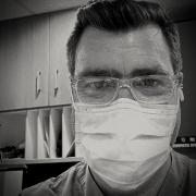 A black and white photo of a man in a medical mask