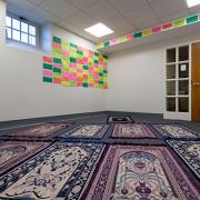 A room with bright colored notes on the wall and prayer rugs on the floor