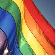 A rainbow flag backlit by the sun