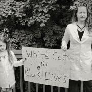 A woman in a doctor's coat and a young child holding a sign that reads White Coats for Black Lives