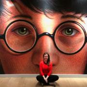 A woman sitting in front of a wall with a the face of Harry Potter looking out at the camera