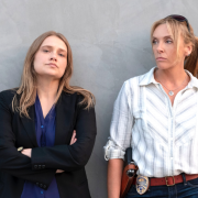 Two women leaning against a wall with intense looks on their faces