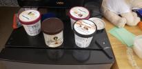 Tubs of ice cream on a frig